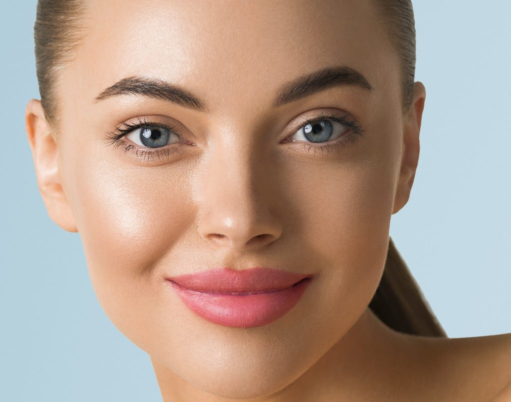 Clean skin woman face close up beauty tanned face beautiful smile. Blue background.