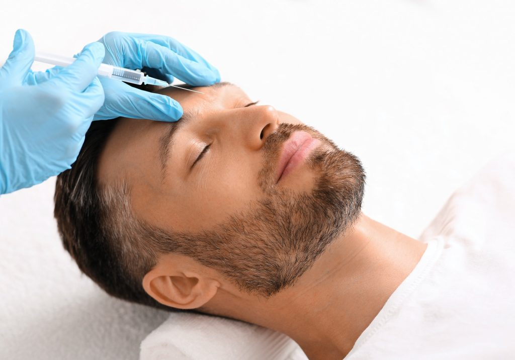 Cosmetologist injecting filler between man brows against frown lines